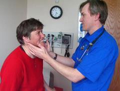 Doctor giving a patient a physical exam for preventative health screening.